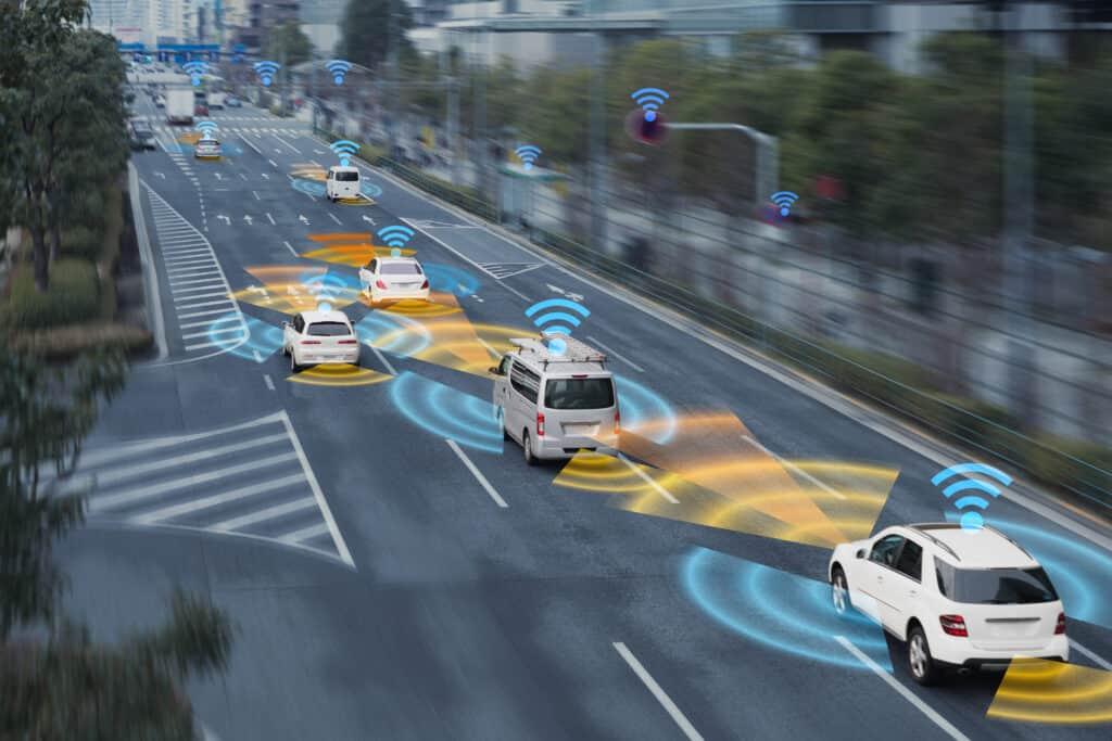 Sinnbild für die Automotive-Branche: Auf einer befahrenen Straße wird druch Wellen-Piktogramme Konnektivität zwischen Fahrzeugen, Straßenlaternen und Ampeln angedeutet.